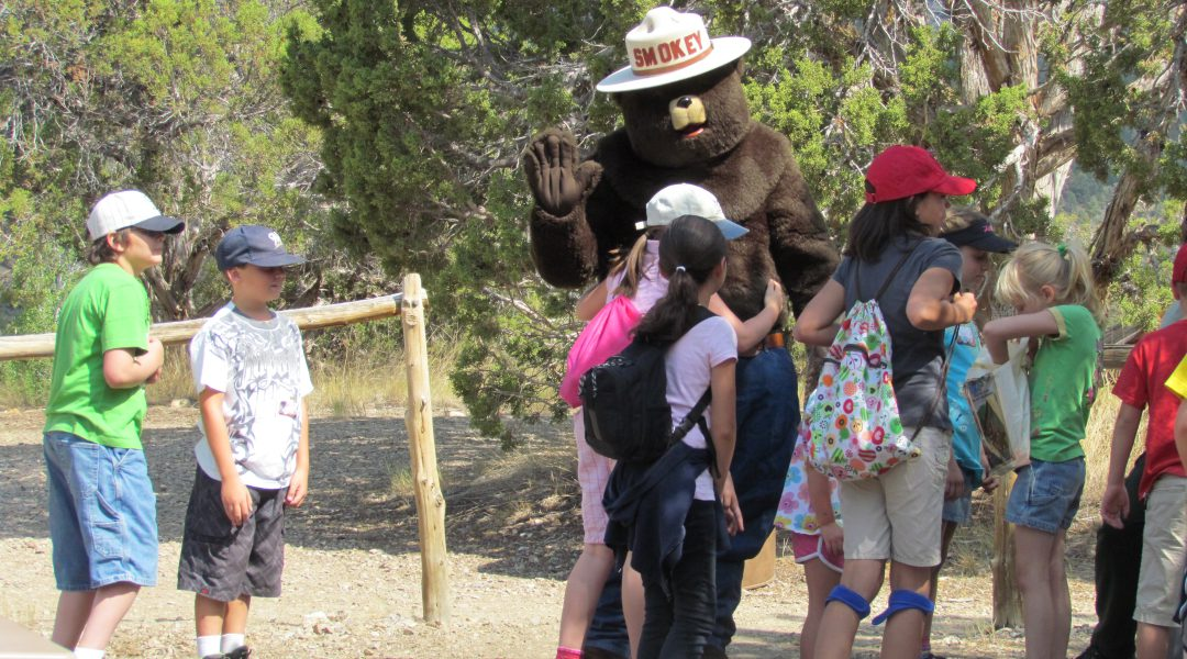 Kids playing with Smokey Bear